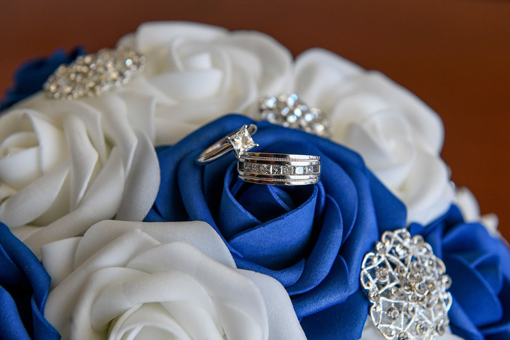 Diamond and silver rings rested on a blue rose