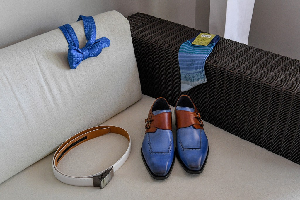 The groom's checkered blue bow tie and leather shoes laid out