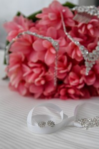 Earrings rest on a white ribbon as diamond necklace rests on a fuschia bouquet