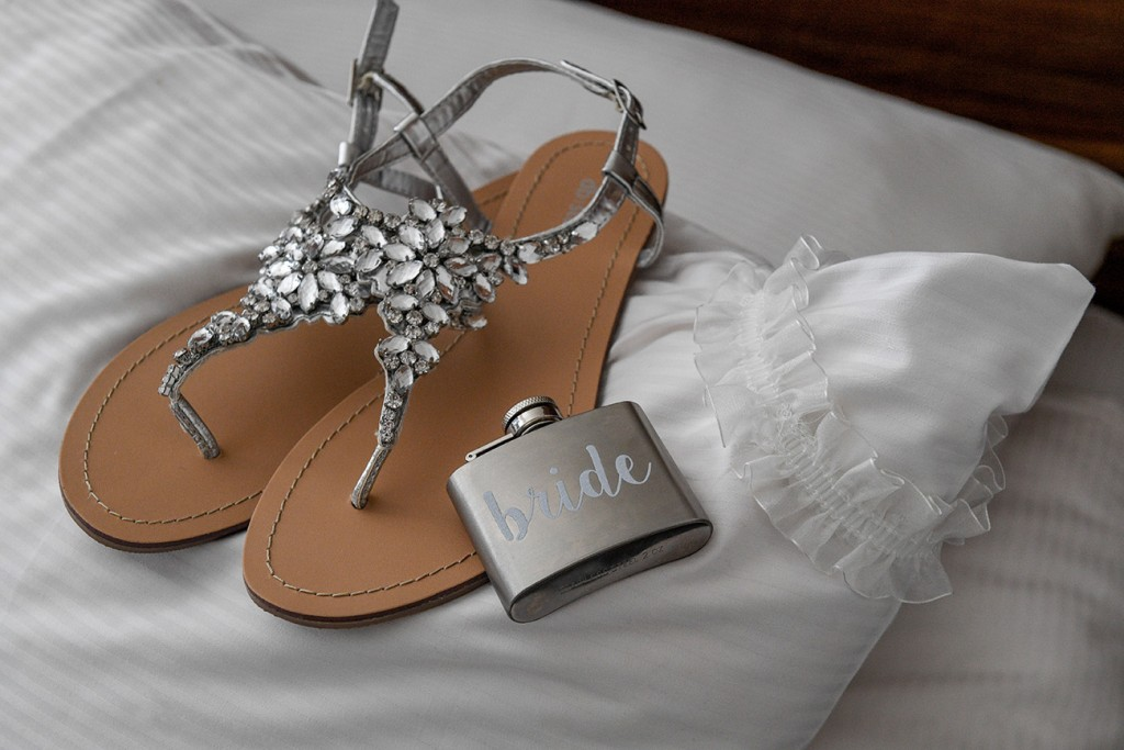 A cute and simple bridal liquor flask rests on simple flat bridal sandals