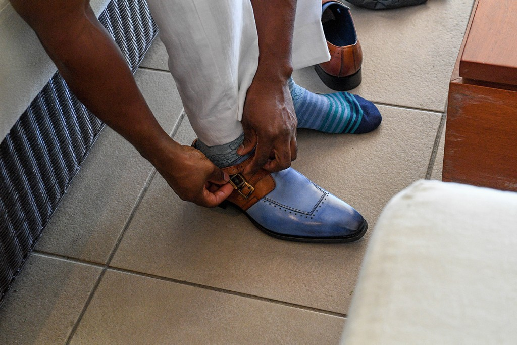 The groom straps up his brown and blue leather shoes