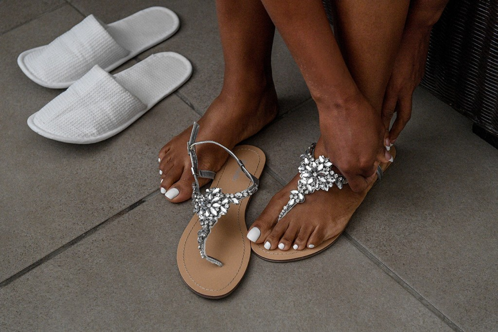 The bride straps on her simple silver sandals