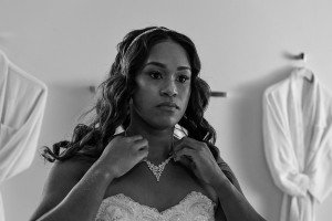 A monochrome photo of the bride admiring her necklace