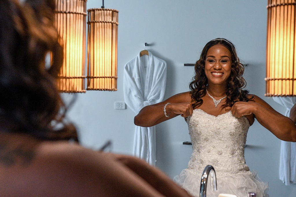 The bride smiles as she admires her reflection in the mirror