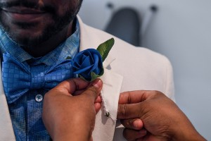 A closeup of a blue rose flower boutonniere being pinned on the grooms lapel