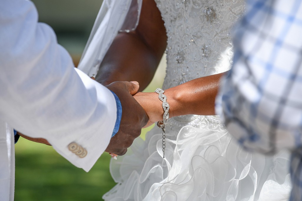 The bride and groom hold hands as they exchange vows