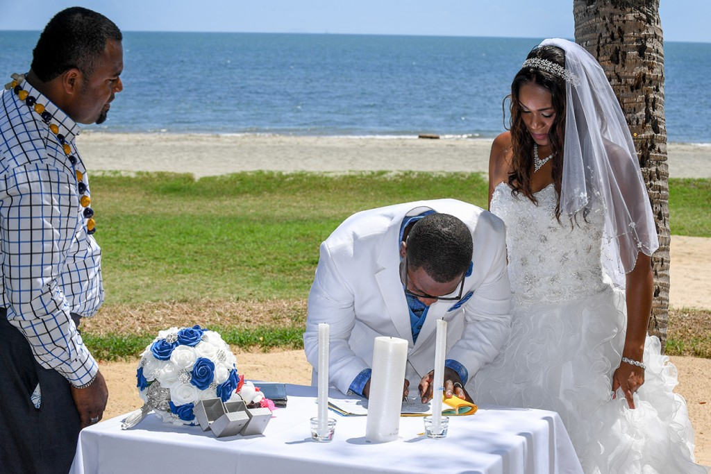 The bride and groom sign their wedding certificates overlooking the beach
