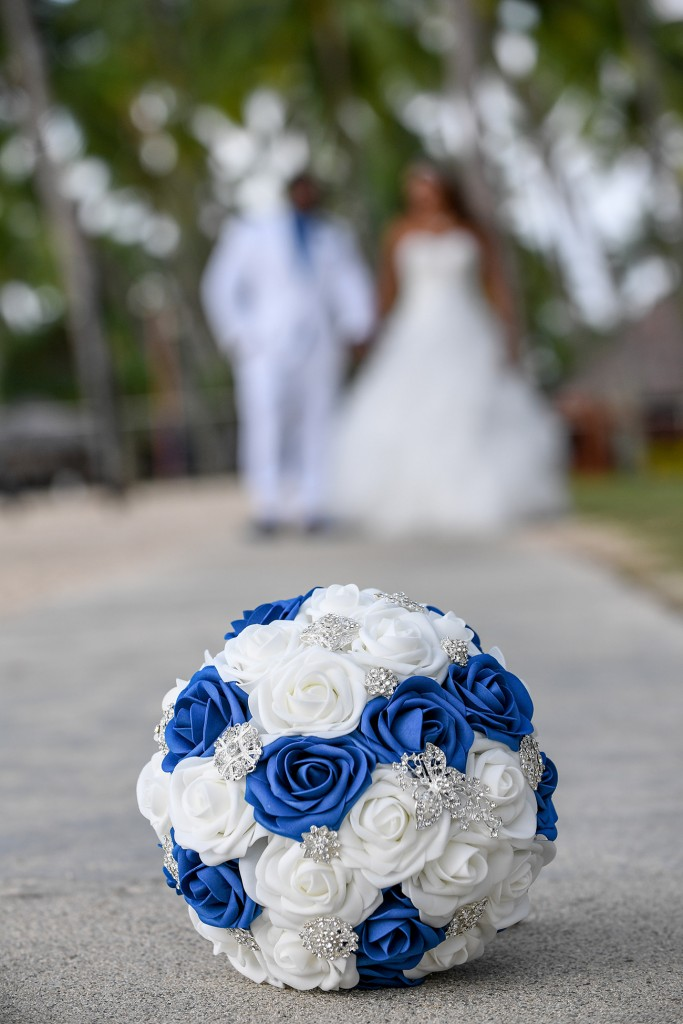 The bride and groom pose behind the Blue and white studded rose bouquet