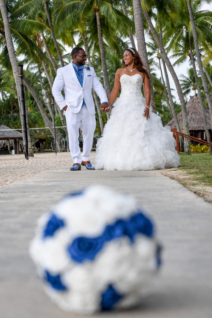 The bride smile behind their blue and white rose bouquet