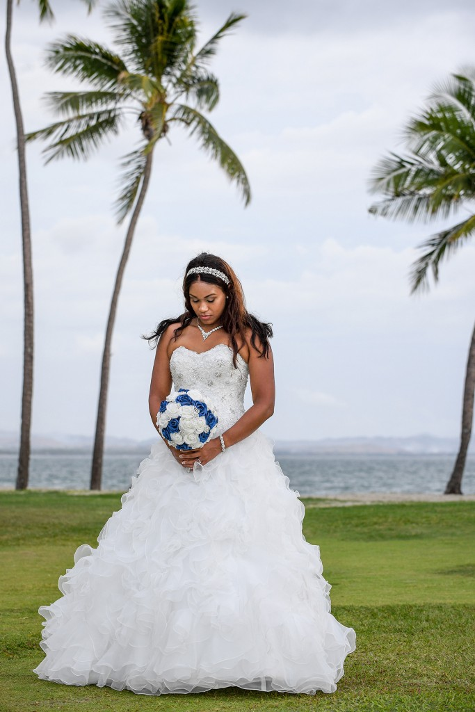The stunning bride stands at the beach holding her blue and white rose bouqet