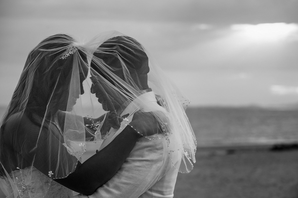 A monochrome photo of the bride and groom under the bride's veil