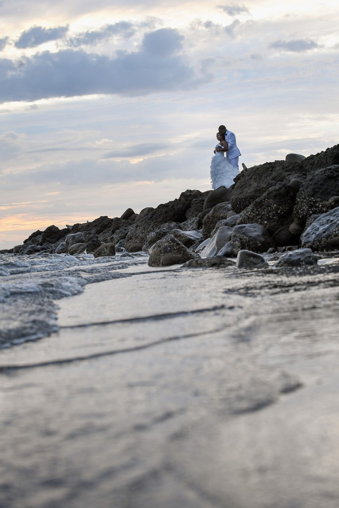 The bride and groom embrace on the rocky shore at sunset