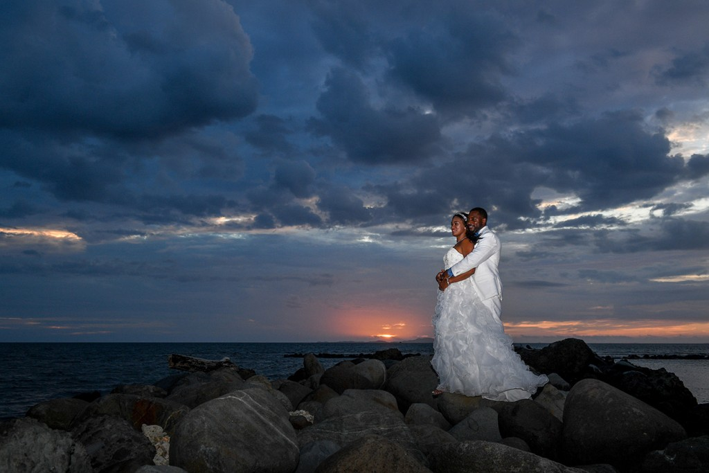 The bride and groom stand on the rocky dock at a pink sunset
