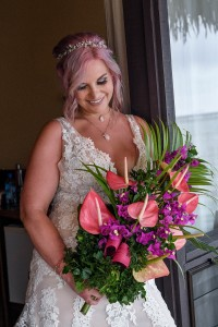 The happy bride poses with her purple and pink flower bouquet