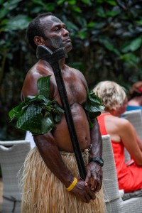 A traditional Fiji warrior in banana leaves and sisal skirt watches on
