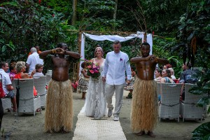 The newly weds walk down the aisle led by traditional Fiji warriors