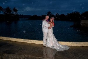 The newly wed couple pose on the dock at sunset