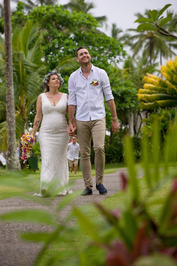 The bride and groom hold hands while walking through the greenery of Warwick Fiji