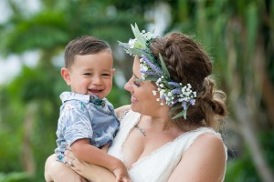 The bride laughs with her son against green palm trees
