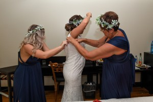 The bride's mother and a bridesmaid help the bride into her wedding gown