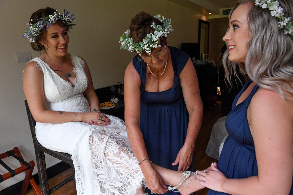 A bridesmaid slips a silver slipper onto the bride's foot
