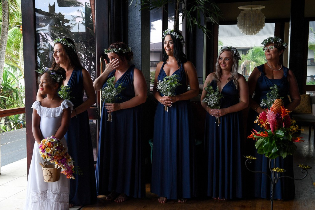 A bridesmaid wipes a tear while at the altar