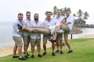 The groomsmen playfully carry the groom above the manicured grass