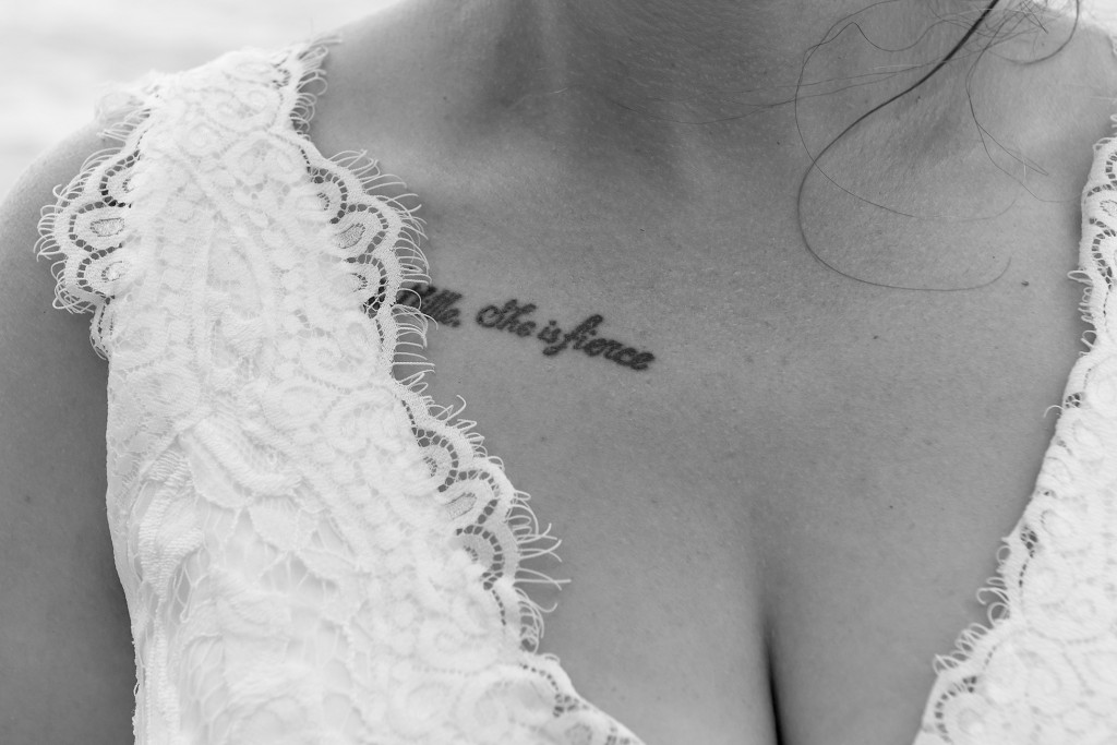 "A closeup on the bride's ""She is fierce"" tattoo"