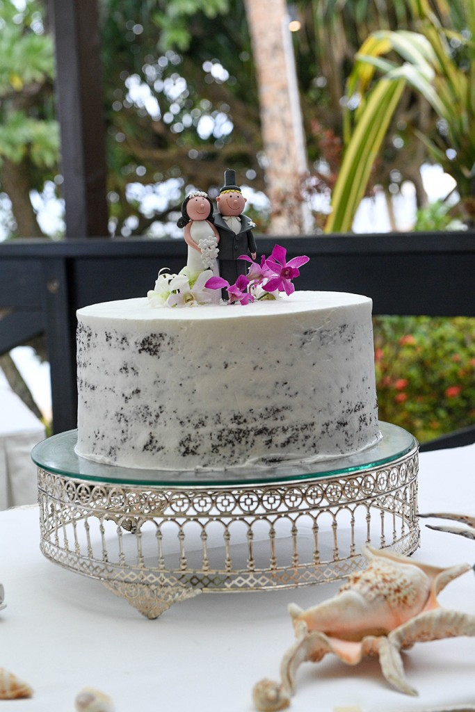 A simple, minimalistic, naked wedding cake with bob head toppers