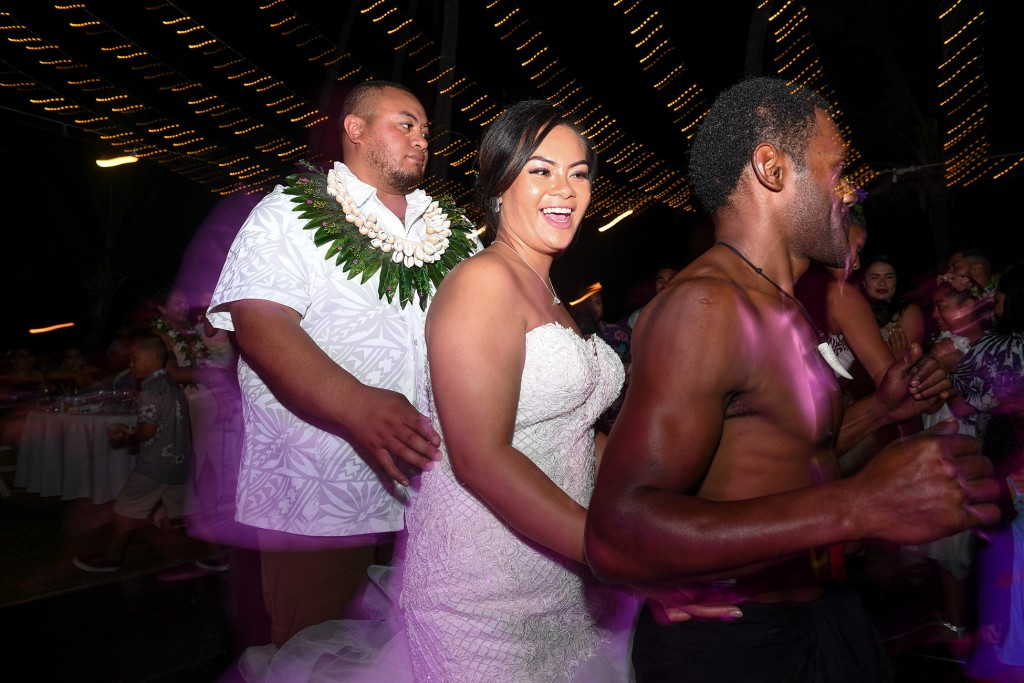 The newly weds dance with traditional Fiji dancers in a conga line under fairy lights