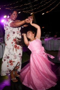 A flowergirl dances with her aunty at the wedding reception