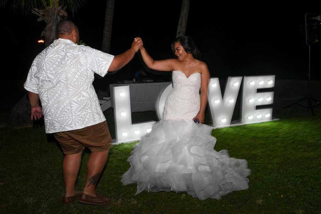 The bride and groom dance against a post sign love
