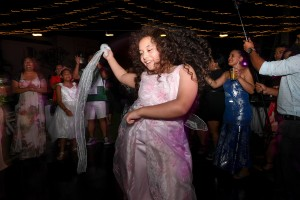 The flower girl dances freely in the under the fairy lights and Fiji night sky at the wedding reception