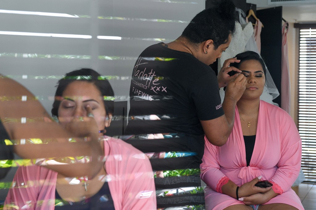 A look of the bridal team having their makeup done through a reflective window