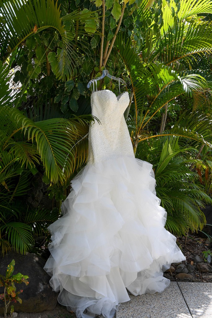 The madrid wedding gown by Sweetheart bridals hanging against palm trees