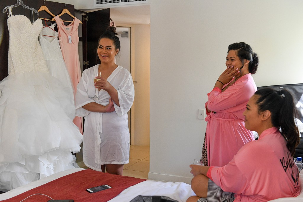 The bridal team admires the bride's wedding gown