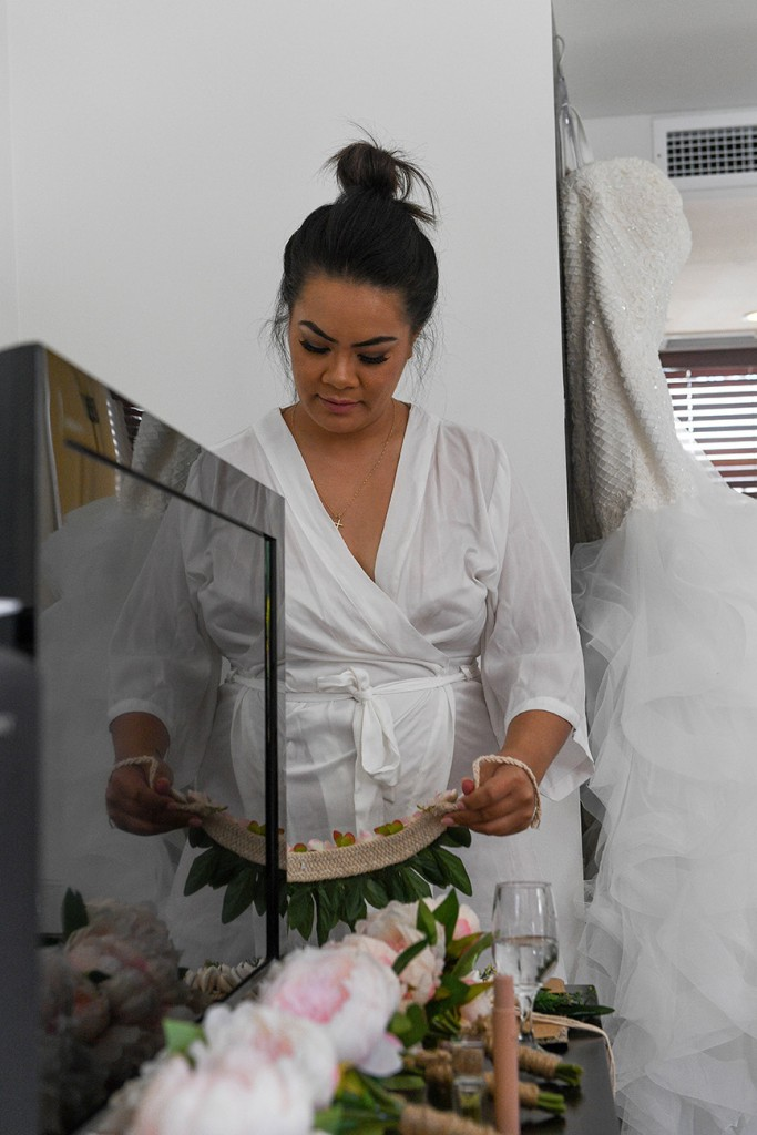 The bride admires a traditional Fiji flower boat