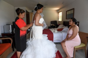 The bride has her gown tied as a bridesmaid watches