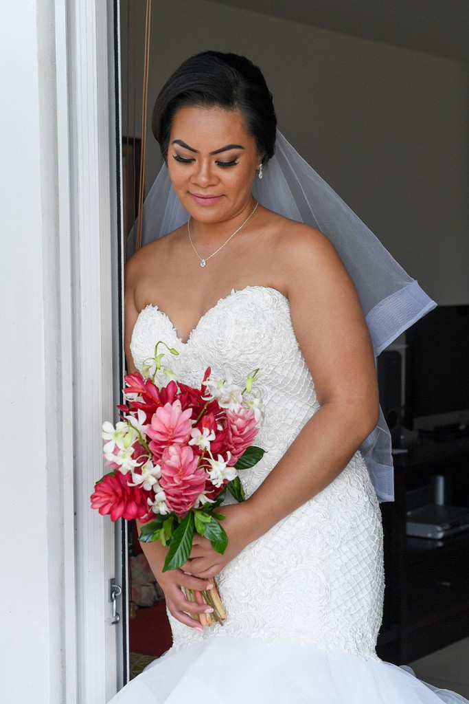 The stunning bride at the doorway with a pink and white ginger and frangipani flower bouquet
