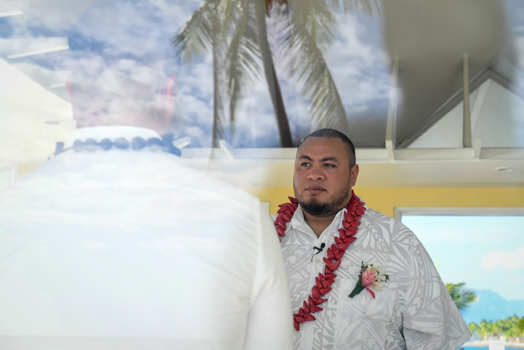 The groom waits nervously with a palm tree reflection in the foreground