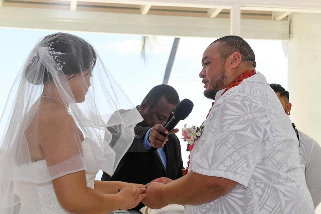The groom says his vows as he puts the ring on his bride's finger