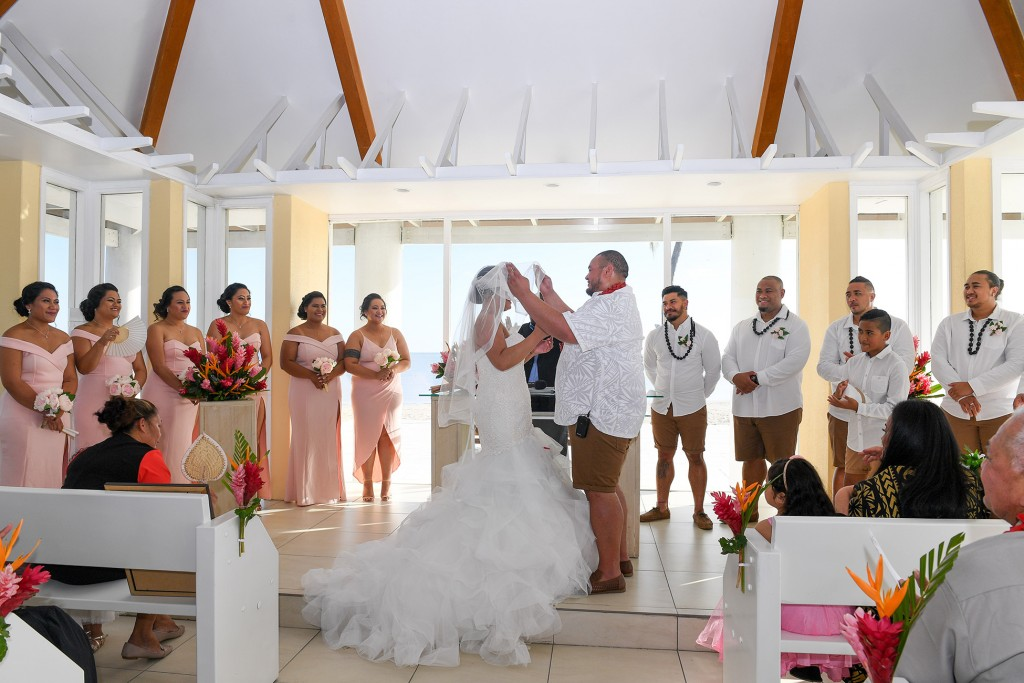 The groom lifts the veil of his stunning bride as the bridal team watches