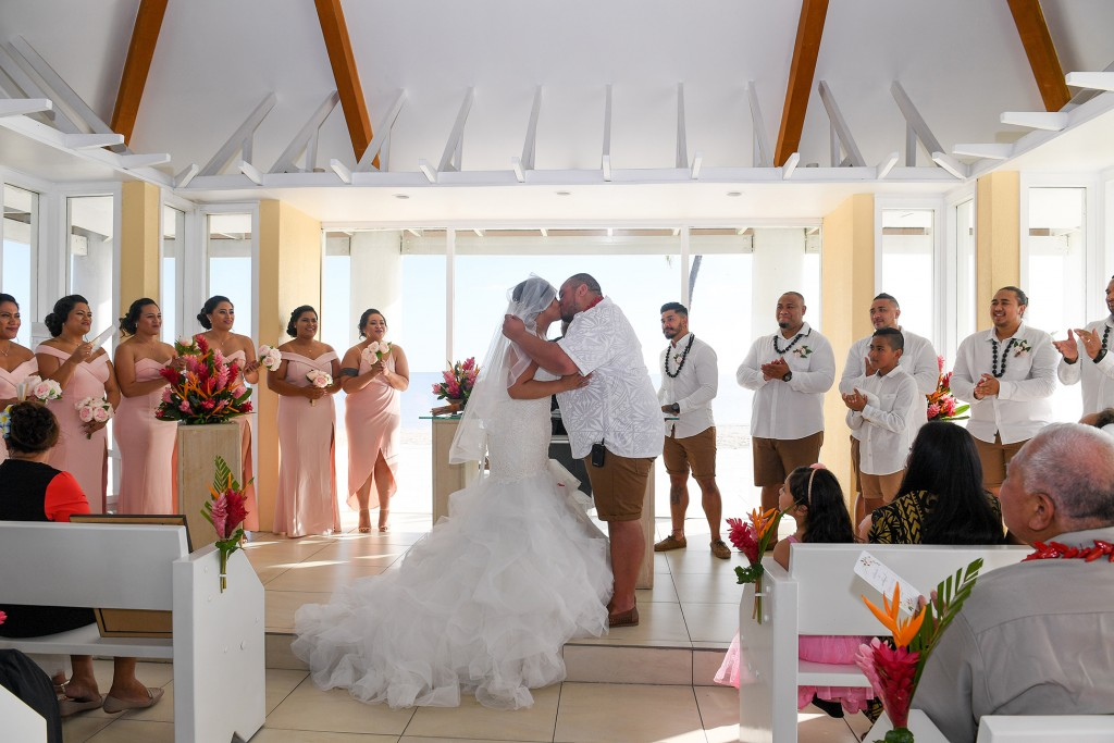 The newly weds kiss as the bridal party cheers