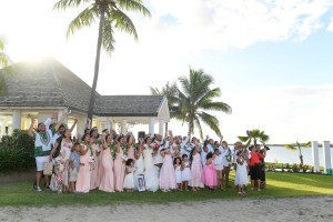Wedding guests wave at the camera on the shores of the Sheraton Fiji