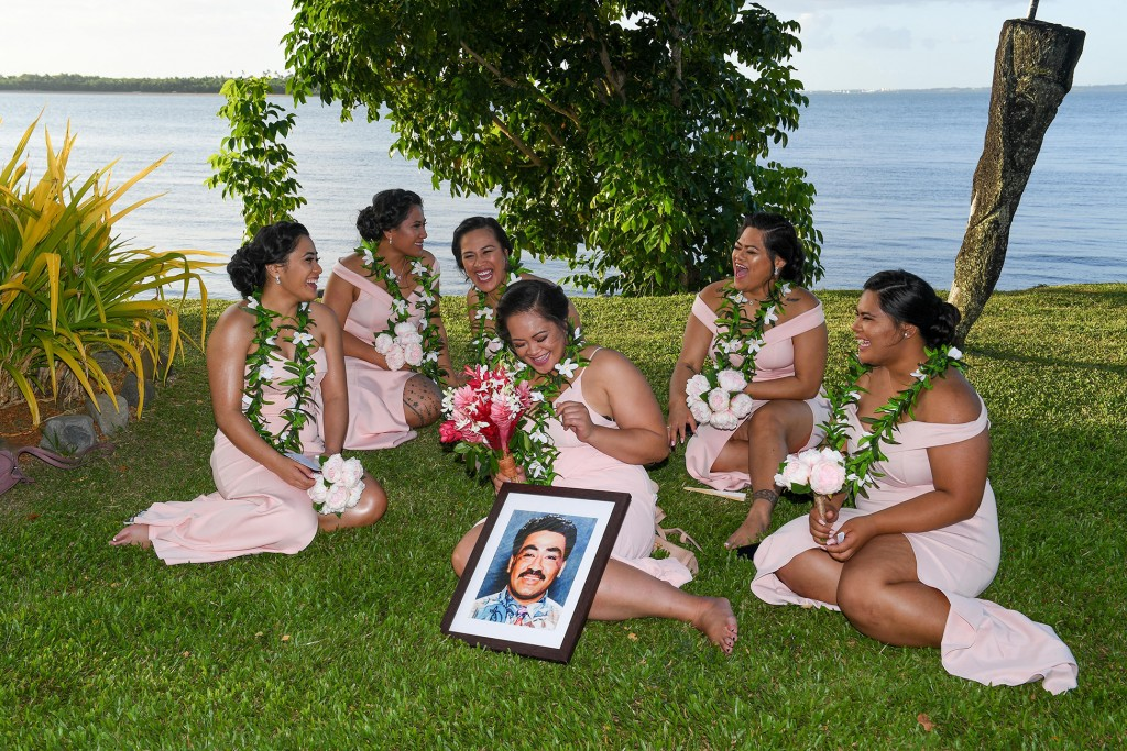 The bridesmaids laugh while seated on the grass seated on the grass against the stunning Pacific ocean