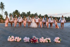 The bridal party poses with their flowers in the foreground on the black sand beach of Sheraton Fiji