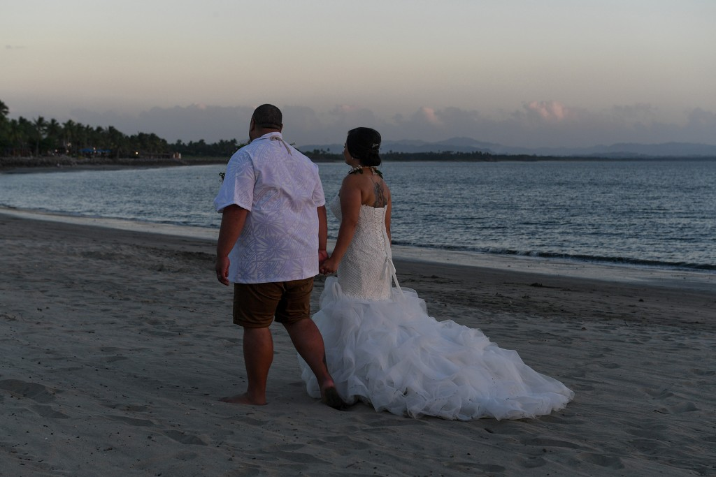 The newly weds stroll on the black sandy beach at sunset