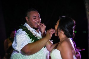 The newly weds feed each other wedding cake under the night sky