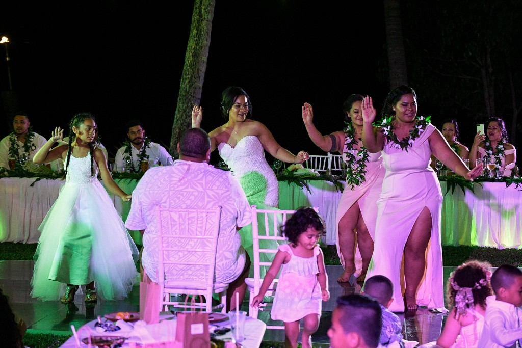 The bride and bridesmaids dance with pink lights reflecting on them at the wedding reception