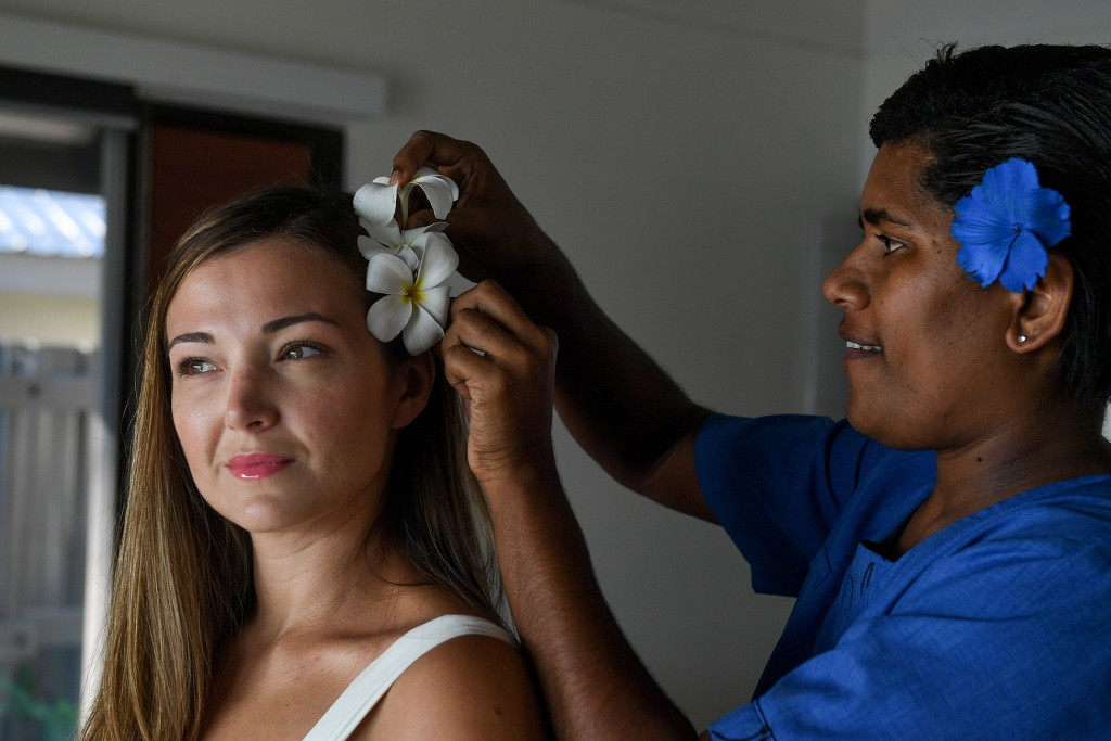 A white frangipani is neatly tucked in the bride's hair